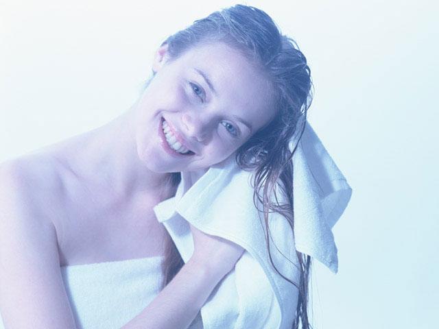 シャンプーの後髪の水気を取っている女性
