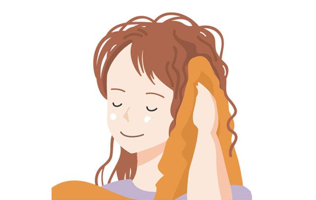 濡れた髪をタオルで乾かしている人