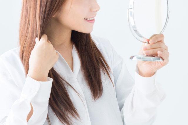 自分の髪をチェックしている女性